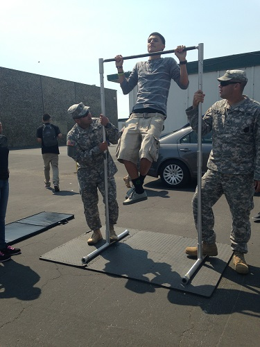 Junior Juan Carlos Alberto Soto does pull-ups to get a water bottle, while Staff Sergeants Michel and Philippi count the number of pull-ups he does. The Army visited  to create awareness of what the army is really about and to provide student with information.