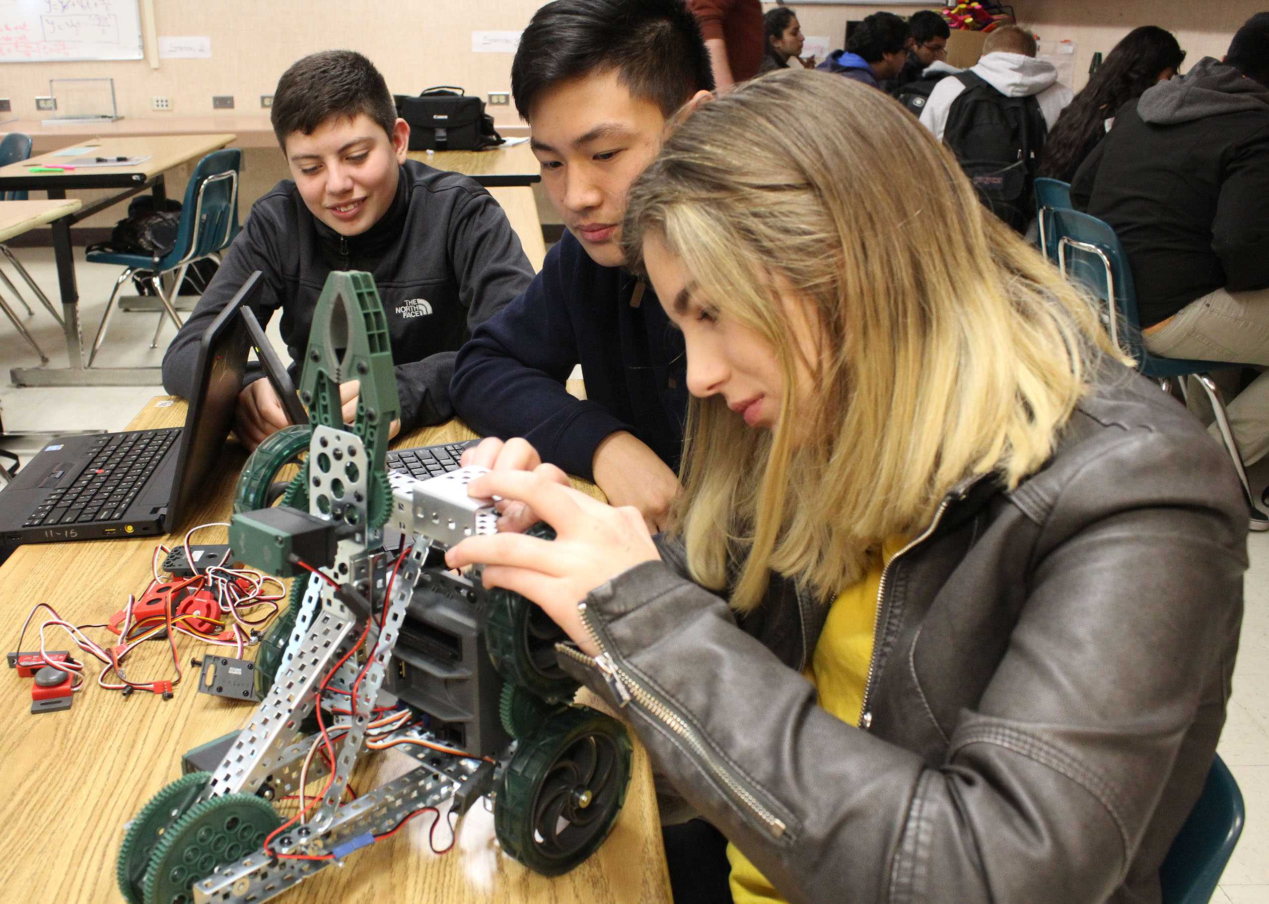 "Junior Kayla Fesy is fitting in the sensors to the robot while Joshua Vuong, freshmen, is observing her work. Fesy said, ""This class is so refreshing! Computer science is super popular in the career field right now. To get to learn about programming and robotics early on is helpful for my future college plans."""
