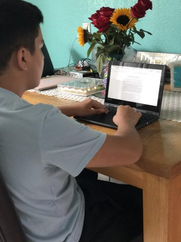 Journalist Arih Mendez doing schoolwork in the kitchen due to space limitations in his bedroom.