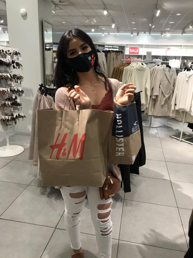 "Junior Stephanie Rodriguez shopping for some clothes to warm her up this fall and winter.  She said, ""I prefer in-store shopping because you get to try on multiple clothes sizes."""
